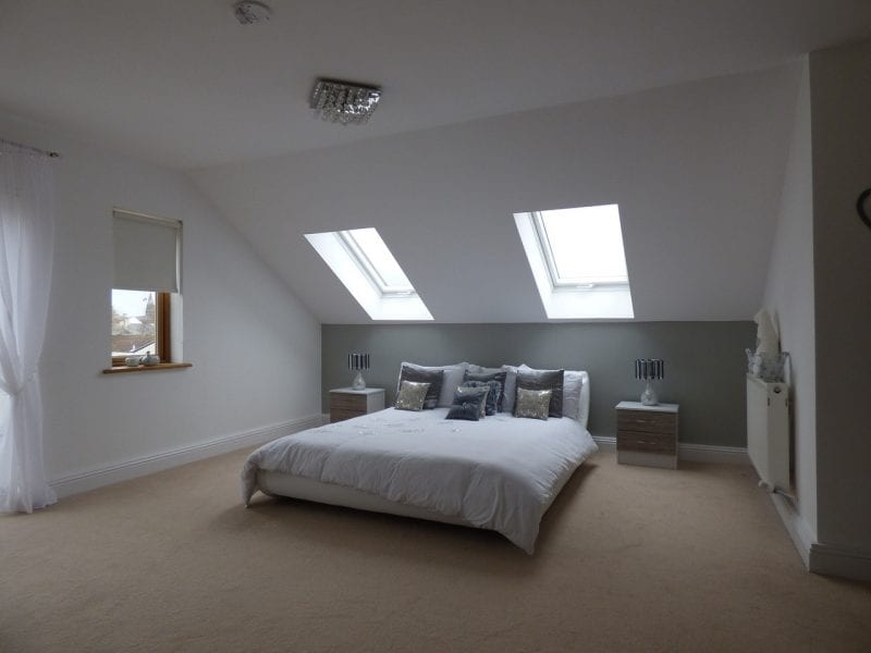 Skylights and windows overlooking large modern style bed