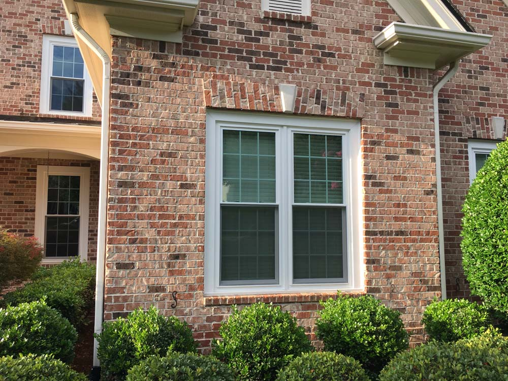 Two double hung windows on brick house