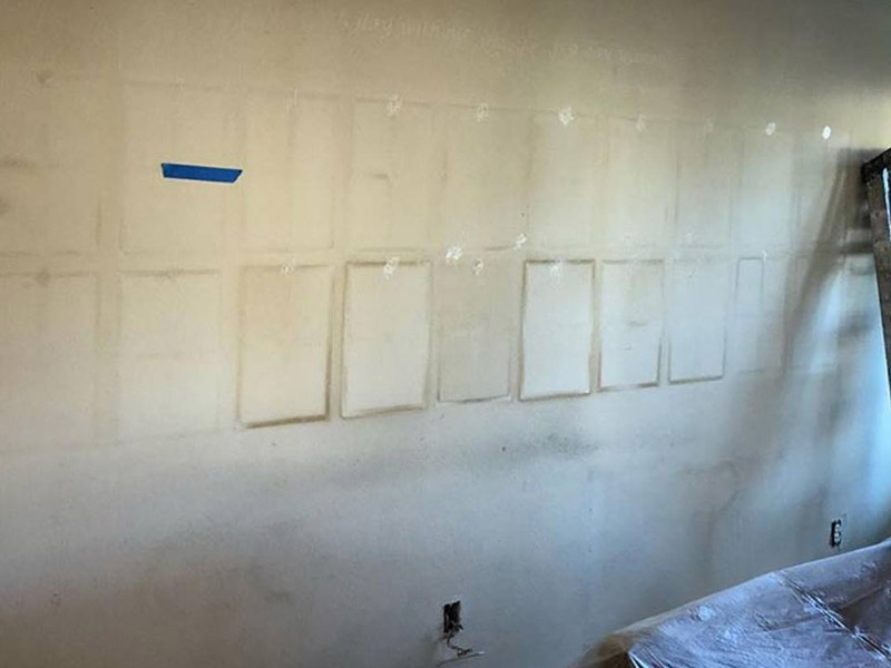 Wall before repainting with stains around where picture frames were