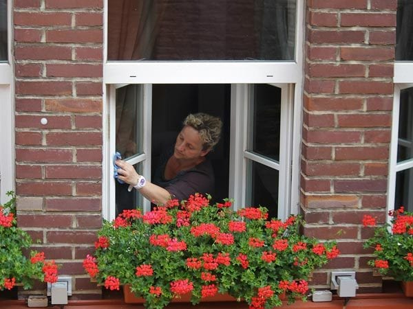 Lady cleaning her house windows